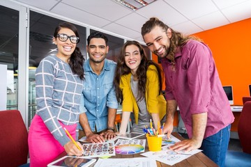 Smiling graphic designers working over photos at desk in office