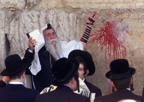 ORTHODOX JEW PRAYS NEXT TO PAINT SPLAT LEFT BY AMERICAN TOURIST AT WESTERN WALL.
