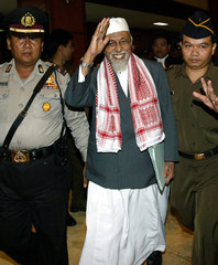 Indonesian Muslim cleric Abu Bakar Bashir waves to supporters while entering a makeshift ...