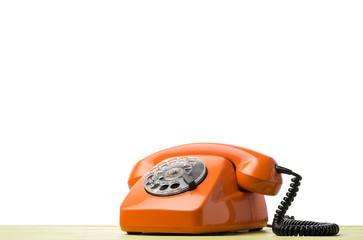 Vintage orange phone on green table