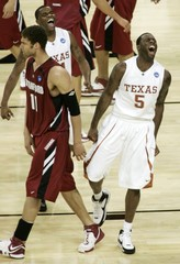 University of Texas guard Damion James and teammate Justin Mason celebrate their victory over Stanford University at game's end in Houston