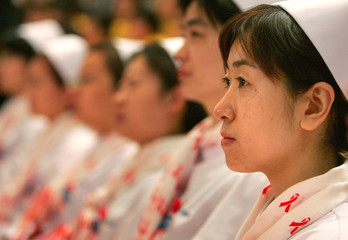 Chinese nurses wear scarves with a red ribbon, the international symbol for AIDS awareness, as they ...