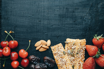 Healthy snacks: strawberries, cherries, dates, almonds, breads, top view, space for text