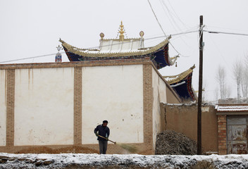 A man clears snow in front of the birthplace of the Dalai Lama in the village of Takser