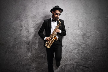 Jazz musician playing saxophone against rusty gray wall