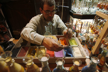 Man scoops coloured sand to fill a glass bottle to create an ornament at his shop in Bab Touma in the Old City of Damascus