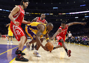 Bryant of the Los Angeles Lakers grabs the ball from Scola, Artest and Brooks of the Houston Rockets during Game 5 of their NBA Western Conference semi-final basketball playoff game in Los Angeles.