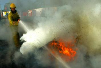 Nicaraguan fire fighter extinguishes burning tires during transportation strike in Managua