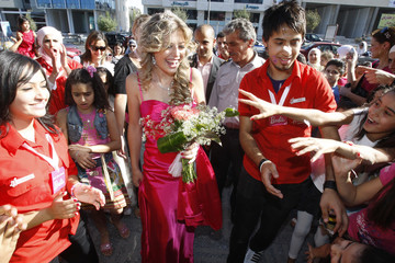 Jordanian model, dressed like Barbie, is cheered by children upon her arrival to a toy store during Barbie's 50th birthday party in Amman