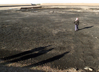AN IRAQI MAN IN BASRA WALKS ON CRUDE OIL RICH SOIL.