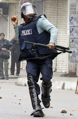 A police officer throws a stone at activists during clashes in Dhaka