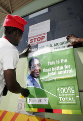 A man sticks an election campaign poster of President Mugabe onto a commuter bus at a local gas station in Bulawayo