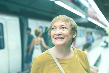 retiree woman passenger in train station .