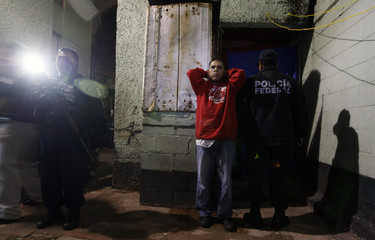 Federal policemen arrest men on suspicion of possessing and distributing drugs during an anti-narcotics operation in Mexico City