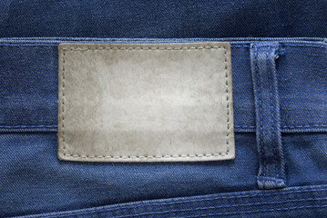Blank grunge dirty leather label on a blue jeans