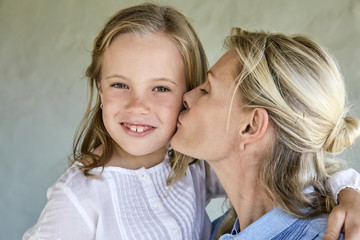 Portrait of smiling little girl kissed by her mother