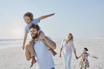 Paar mit zwei Kindern laufen am Strand entlang