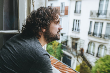 Man looking through opened window at home