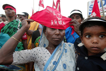 Indian tribal woman ties communist party flag during election campaign meeting near Midnapore