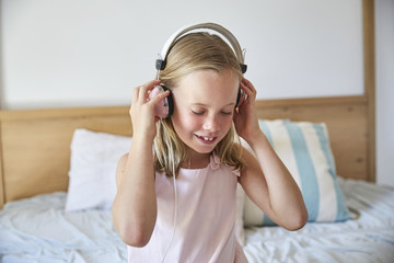 Portrait of smiling little girl listening music with headphones at home