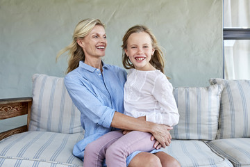 Portrait of smiling little girl sitting on mother's lap