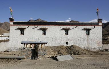 A Tibetan man spins prayer-wheels outside a traditional house near the city of Shigatse