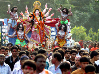 Devotees pull a cart carrying a statue of the Goddess 'Durga' to the river Buriganga in Dhaka