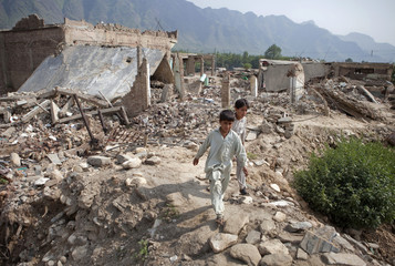 Boys walk through the rubble of destroyed homes in Buner district
