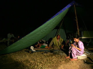 Kashmiri family lives under a tent inside a stadium after their house was damaged by an earthquake in Muzaffarabad
