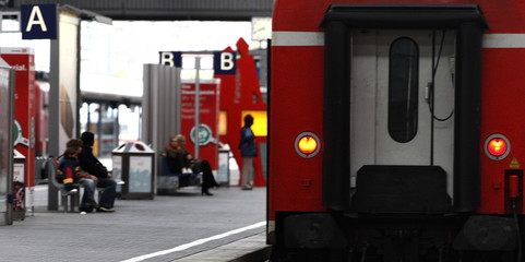 Passengers wait for a train during a warning strike in Munich