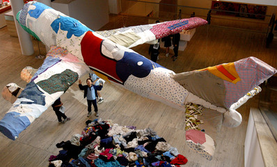 A YOUNG BOY LOOKS UP AT A PLANE MADE FROM OLD CLOTHES DURING BIENNALE EXHIBITION IN SYDNEY.