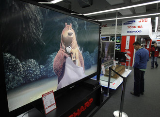 "A shopper stands near a 108"" LCD television set on display at a store in Budapest"