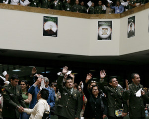Police officers Armando Castellanos, Julio Buitrago, John Duran and Javier Rodriguez wave to their comrades at the National Police building in Bogota