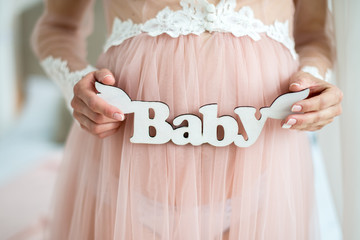 A pregnant woman is holding a wooden sign baby. Closeup