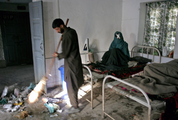 Man sweeps hospital ward as injured woman sits on a bed in Karnah