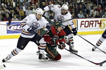 Oilers Stortini and Reasoner fight for puck with Wilds Smith