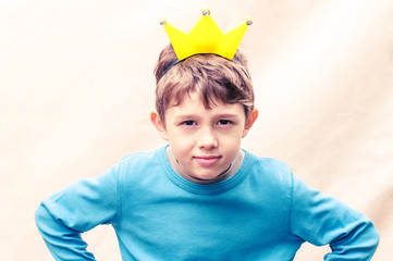 A boy with a crown on his head on a light background