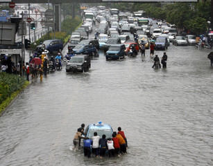 Residents push a taxi in a flooded street in central Jakarta