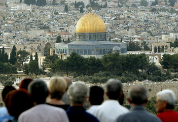 Tourists stand on the Mount of Olives overlooking the Old City of Jerusalem with the golden Dome of ...