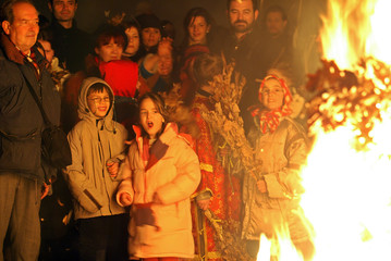 People watch a ceremonial burning of dried oak branches the Yule log symbol for the Orthodox ...