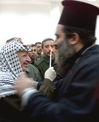 FATHER ATTALLAH HANA HUGS PALESTINIAN PRESIDENT YASSER ARAFAT DURING ACHRISTMAS CEREMONY IN HIS ...