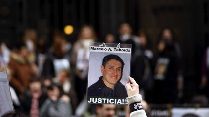 A relative of victims of a nightclub fire holds up an image of the victim as she awaits the verdict outside the Justice building in Buenos Aires