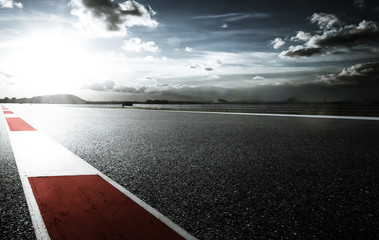 Racetrack with red and white safety sideline ,dramatic cloudy sky and cold mood filter apply .