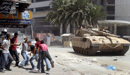 PALESTINIAN YOUTH HURL STONES AT AN ISRAELI TANK DURING CLASHES IN THEWEST BANK CITY OF NABLUS.