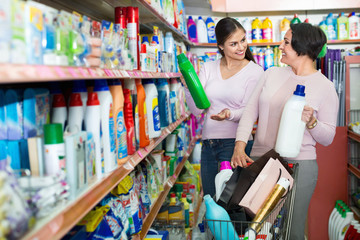 Young girl and mature woman choosing washing detergent