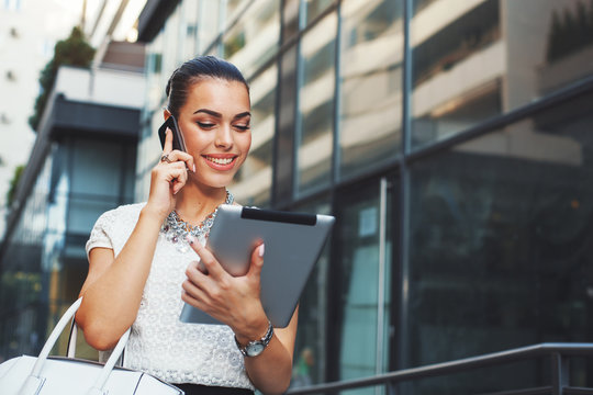 Young businesswoman talking on the phone with digital tablet in hand outdoor