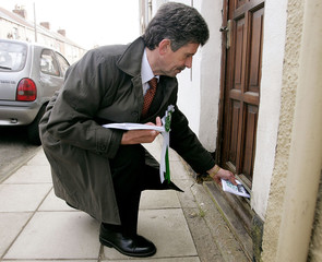 Independent candidate Keys delivers leaflets as he campaigns in the constituency of Britain's Prime ...