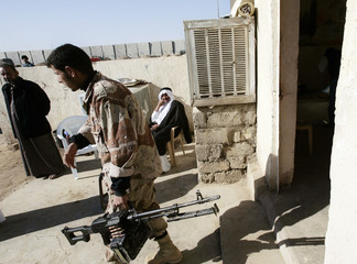 An Iraqi soldier carries a machine gun before going on patrol with the 101st Airborne Division Air Assault, in Bayji