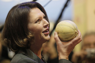 German Consumer Protection Minister Aigner smells a fruit one day before the official opening of the 'Internationale Gruene Woche/International Green Week (IGW)' fair in Berlin