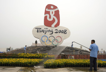 A worker waters a flower installation at the base of a giant 2008 Beijing Olympic logo at Beijing's Tiananmen Square
